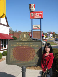 Apple posing in front of the KFC birthplace monument